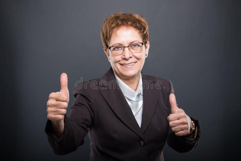 La dame supérieure d'affaires montrant le double aiment le geste photos stock