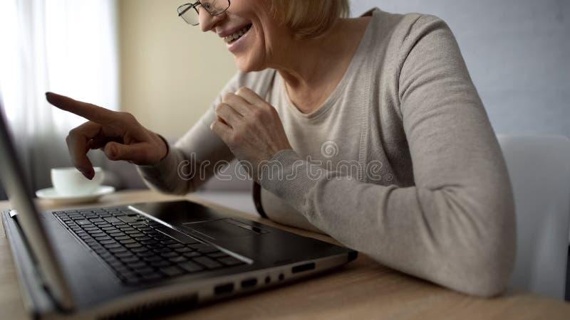 La dame supérieure a enchanté pour parler aux enfants dans l'Internet, regardant l'écran d'ordinateur portable photos libres de droits