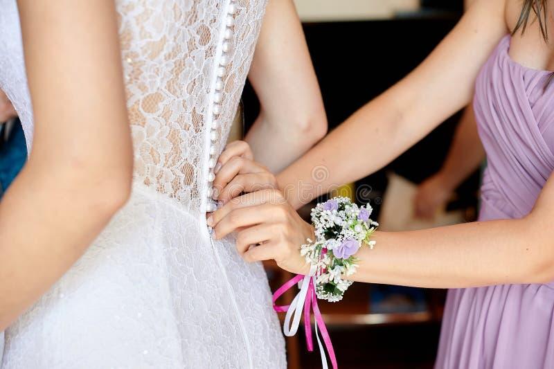 La damigella d'onore aiuta la sposa a portare il vestito fotografie stock