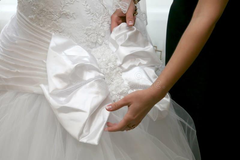 La damigella d'onore contribuisce a correggere l'arco sul vestito la sposa fotografie stock