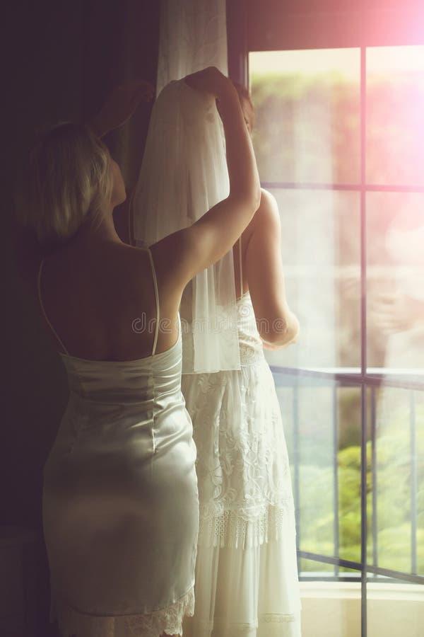La damigella d'onore graziosa aiuta la bella sposa a mettere sopra il velo immagini stock libere da diritti