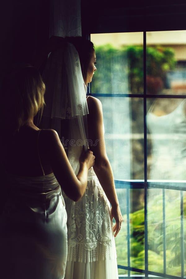 La damigella d'onore graziosa aiuta la bella sposa a mettere sopra il velo immagine stock libera da diritti