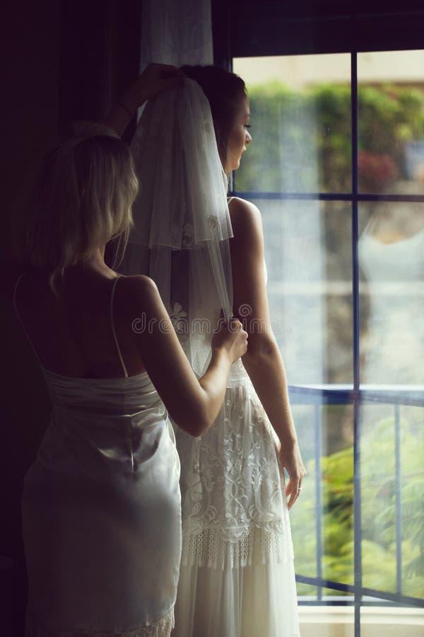La damigella d'onore graziosa aiuta la bella sposa a mettere sopra il velo fotografie stock libere da diritti