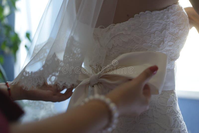La damigella d'onore si agghinda il corsetto della sposa fotografie stock