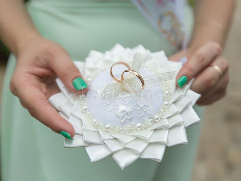 La damigella d'onore tiene il cuscino dell'anello con le fedi nuziali dorate di paia fotografie stock libere da diritti