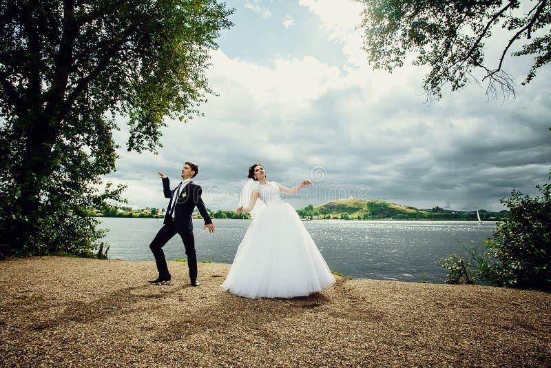 La danse de jeunes mariés leur joyeuse danse l'épousant sur le rivage de l'étang photos libres de droits