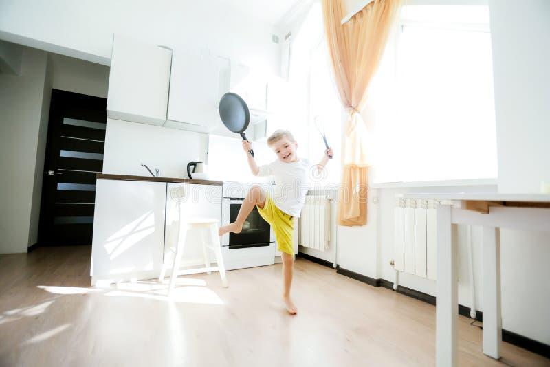 La danse européenne drôle de chef de petit garçon, week-end heureux, garçon veut faire des crêpes, mais la poêle sont trop gaie,  photos libres de droits