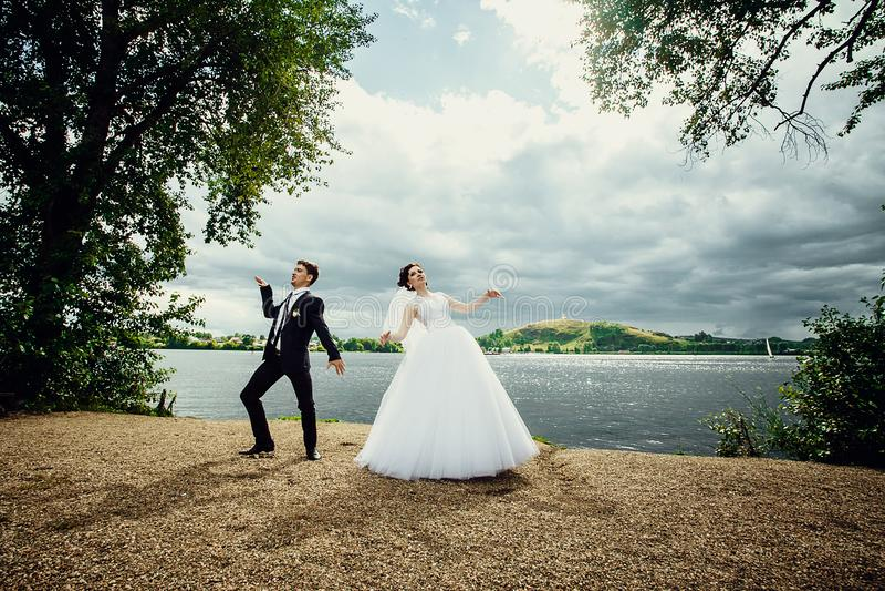 La danza de novia y del novio su feliz danza que se casa en la orilla de la charca fotos de archivo libres de regalías