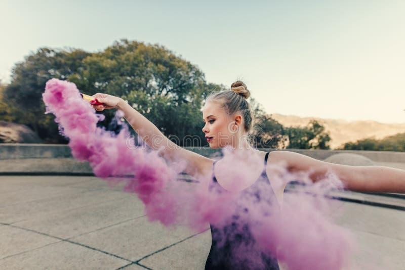 La danza practicante femenina del bailarín de ballet se mueve usando una bomba de humo imagen de archivo libre de regalías