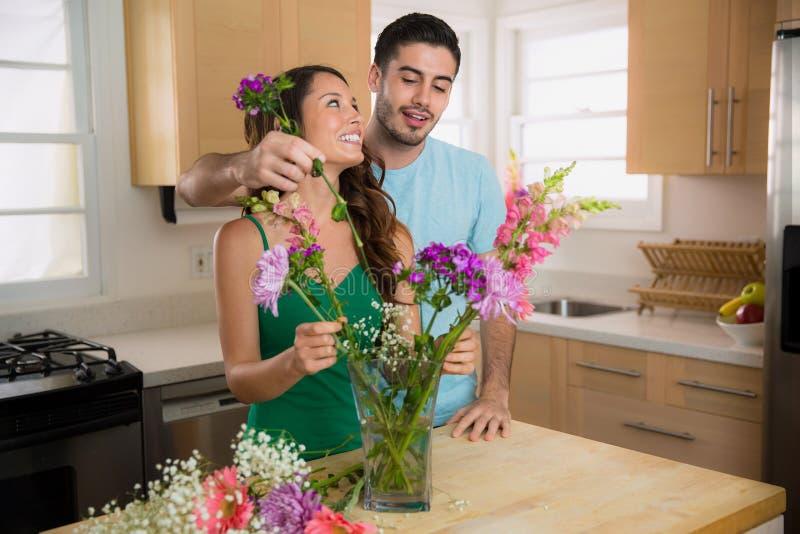 La datation d'homme espiègle et de femme a mis des fleurs dans un vase à la maison dans la cuisine photographie stock libre de droits