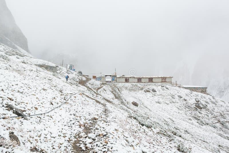 La de Thorong, Nepal - 15 de octubre: Sherpa que entrega fuentes al campo bajo de la mucha altitud en 4540 m en ventisca de la ni fotografía de archivo