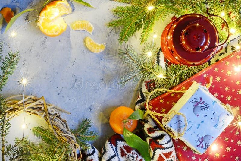 La decoración con las velas, linterna, pino de la Navidad ramifica, los conos del pino, bolas guirnalda, regalo en fondo de mader fotografía de archivo