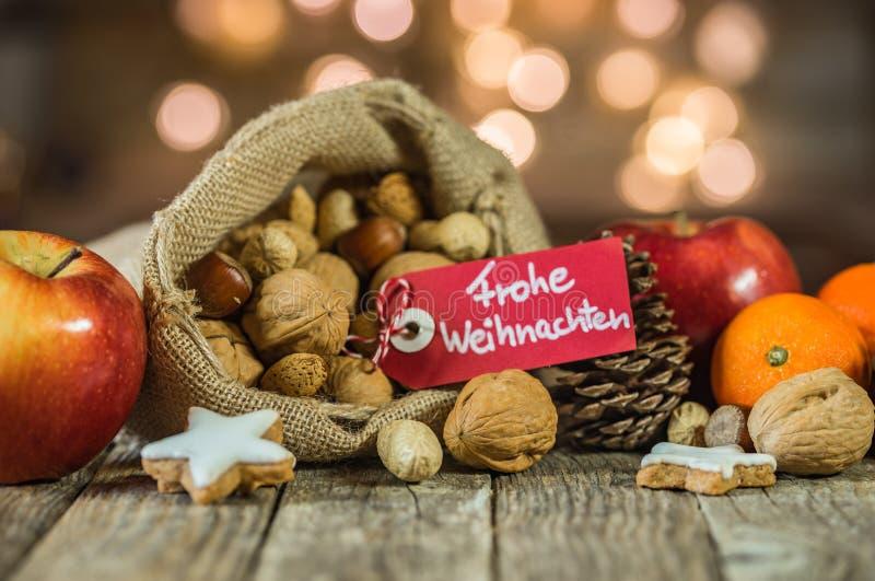 La decoración de la comida del advenimiento y de la Navidad con la etiqueta y el texto alemán, Frohe Weihnachten, significa Feliz fotos de archivo