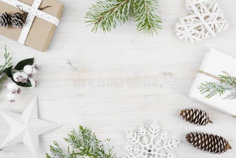 La decoración de la Navidad, regalo, heló las ramas del ciprés, conos del pino Fondo de madera fotografía de archivo libre de regalías