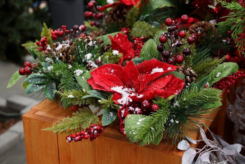 La decoración del Año Nuevo en una cesta de ramas coníferas verdes, de hojas rojas y de bayas debajo de la nieve blanca en la tab foto de archivo