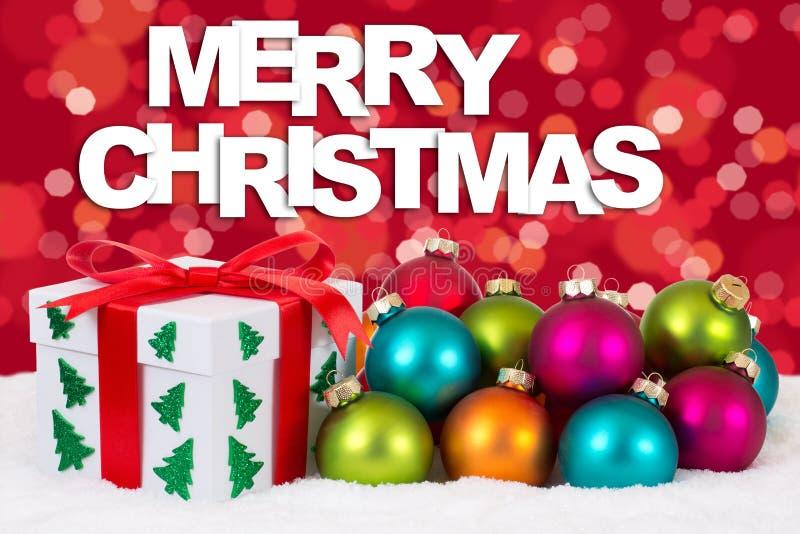 La decoración del carte cadeaux de la Feliz Navidad con el fondo rojo se enciende fotografía de archivo