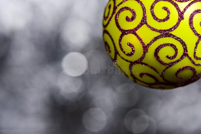La decoración festiva para el árbol de navidad, bola amarilla con la decoración del brillo en gris empañó el fondo, cierre para a imágenes de archivo libres de regalías