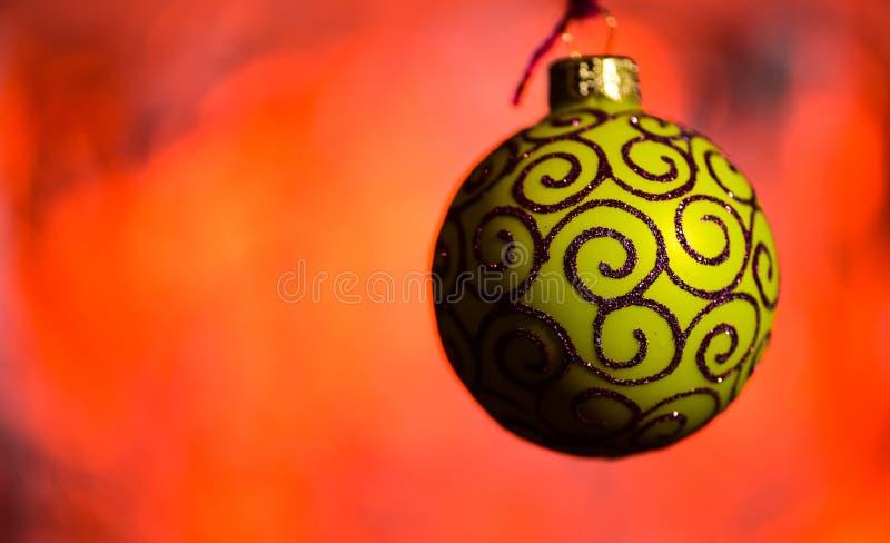 La decoración festiva para el árbol de navidad, bola amarilla con la decoración del brillo, en rojo empañó el fondo Concepto del  imagen de archivo