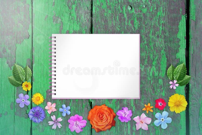 La decoración hermosa florece el marco con el cuaderno en el centro en fondo de madera pintado lamentable anaranjado de los escri fotografía de archivo