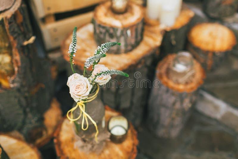 La decoración rústica de la boda, botella adornada con subió en el tocón fotos de archivo libres de regalías