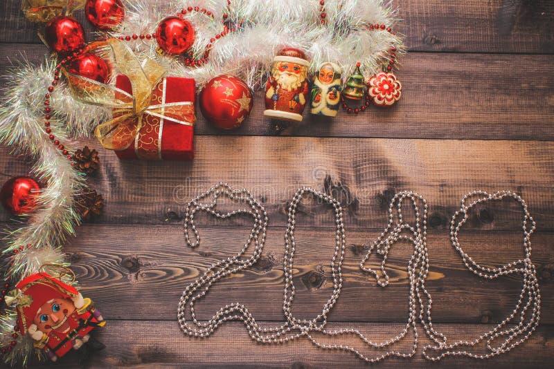 La decoración y los juguetes festivos del Año Nuevo en una tabla de madera con una caja roja de la secuencia con un regalo Santa  imágenes de archivo libres de regalías