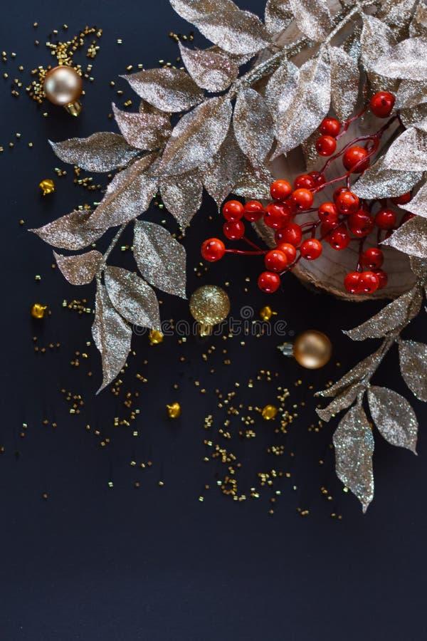 La decorazione dell'oro natalizio su sfondo scuro Bauble, more rosso e foglie d'oro Piastra piatta fotografie stock