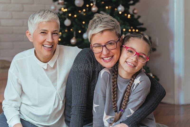 La decorazione della nipote e della nonna Natale treeFamily si è riunita intorno ad un albero di Natale, generazioni femminili immagine stock