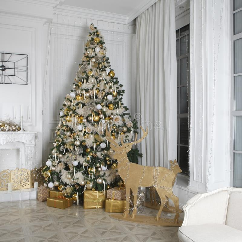 la decorazione della stanza di Natale Abete rosso con i regali Figure di legno dei cervi con luce Camino decorato con una corona  fotografia stock