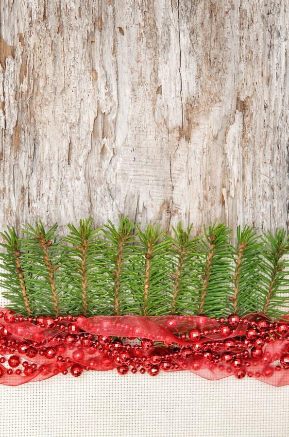La decorazione di Natale con la ghirlanda rossa, la tela e l'abete si ramificano immagini stock libere da diritti