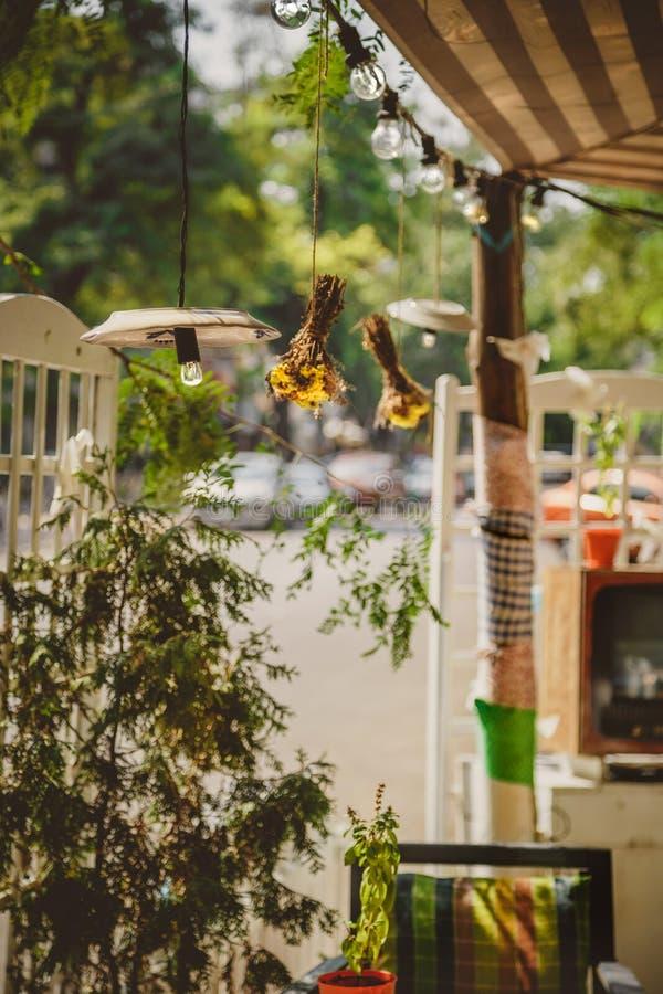 La decorazione, retro corda d'annata all'aperto accende l'attaccatura in una linea in caffè Decorazione di illuminazione fotografia stock libera da diritti