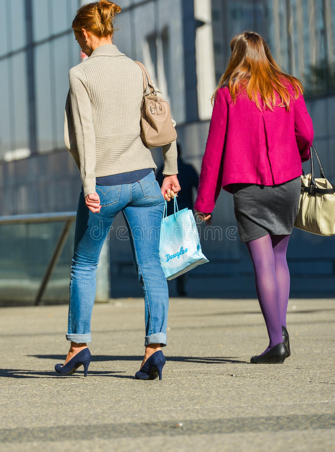 La defense, France- April 10, 2014:back view of two casual workers walking on a street. One wears pumps and the other black stock photos