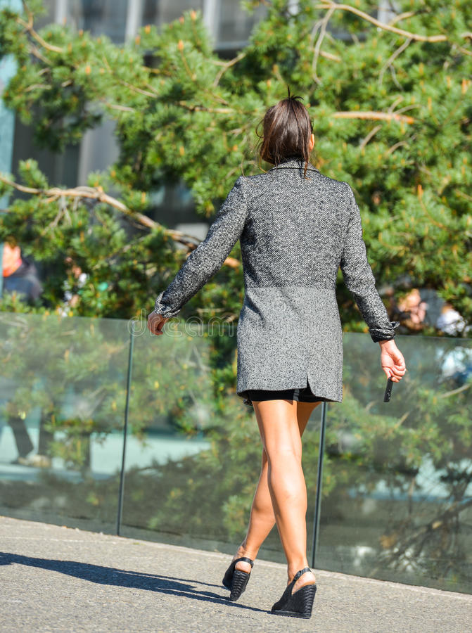 La defense, France- April 10, 2014:portrait of a business woman walking on a street. She looks very casual, wears short skirt stock photo