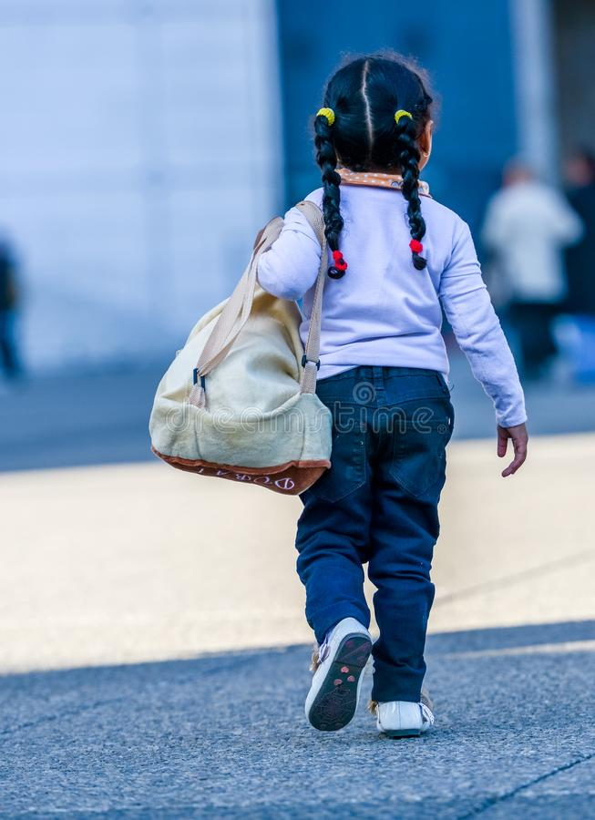 La defense, France - April 9, 2014: Rear view of child walking on city road royalty free stock photo