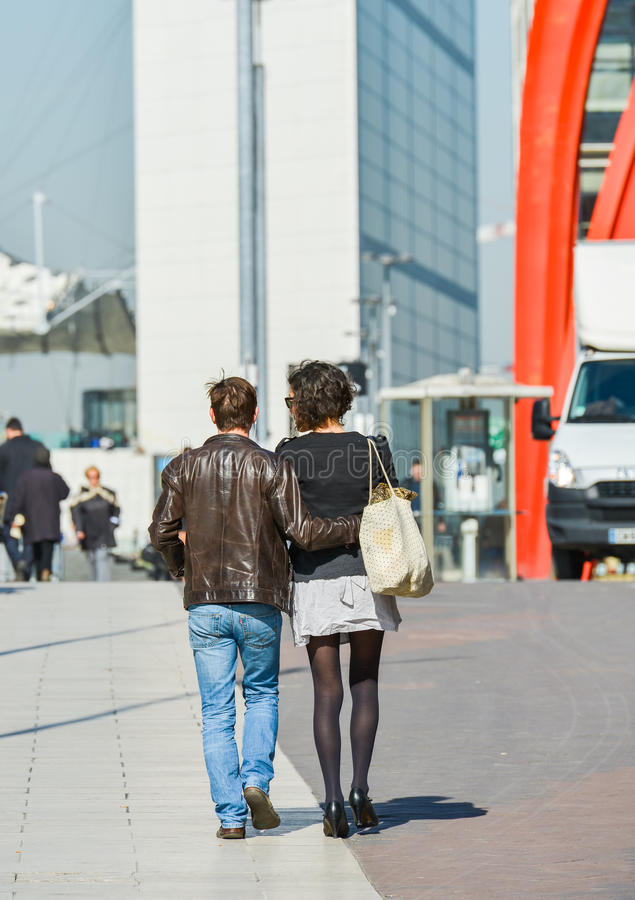 La defense, France- April 10, 2014: Stylish couple walking in a street. The man is wearing blue jean's and the woman short grey sk royalty free stock photo