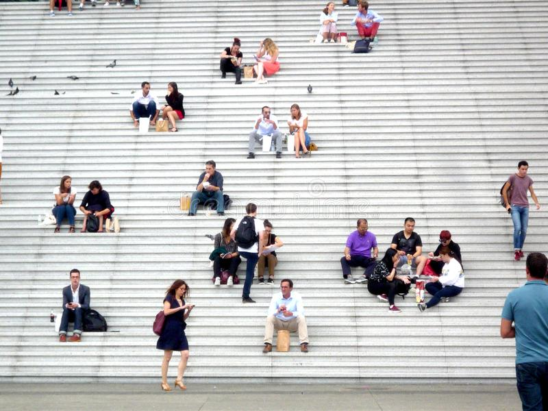 La Defense, Paris,, France, August 20 2018: people sitting and walking on the stairs of the Grand Arch stock photography