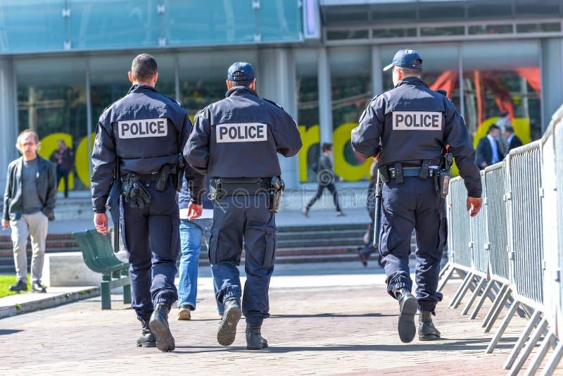 La-defensie, Frankrijk 10 April, 2014: Achtermening van boompolitiemannen die in het centrum van La-defensie lopen, groot bedrijf stock foto