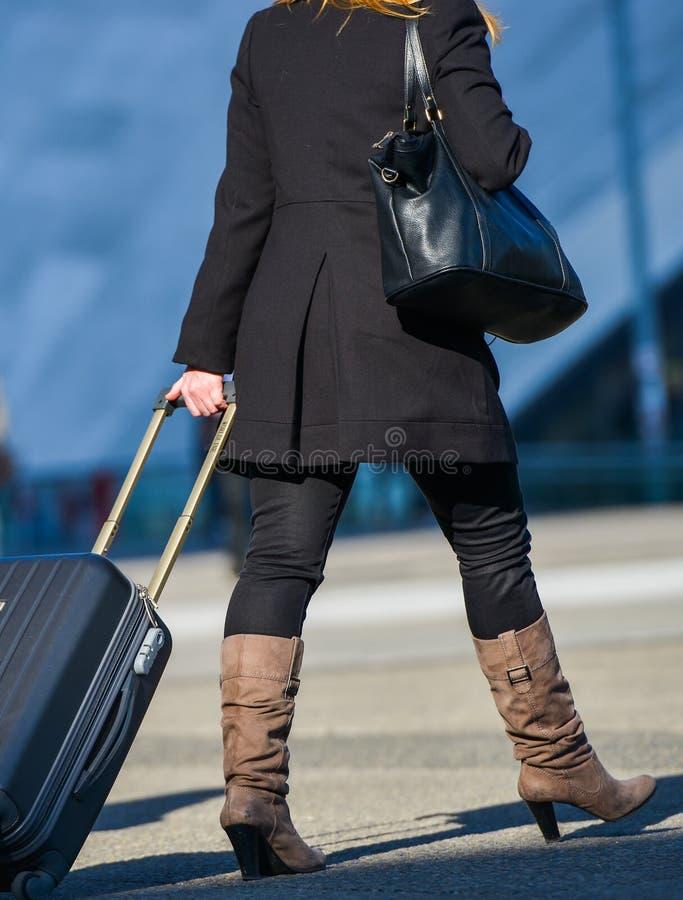 La-defensie, Frankrijk 09 April, 2014: Handelsreiziger die onderaan de straat lopen en koffer trekken Zij draagt lange laarzen, z stock foto's