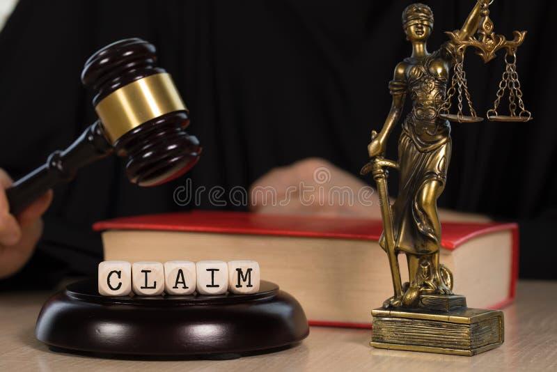 La DEMANDA de la palabra integrada por de madera corta en cuadritos Mazo y estatua de madera de Themis en el fondo foto de archivo