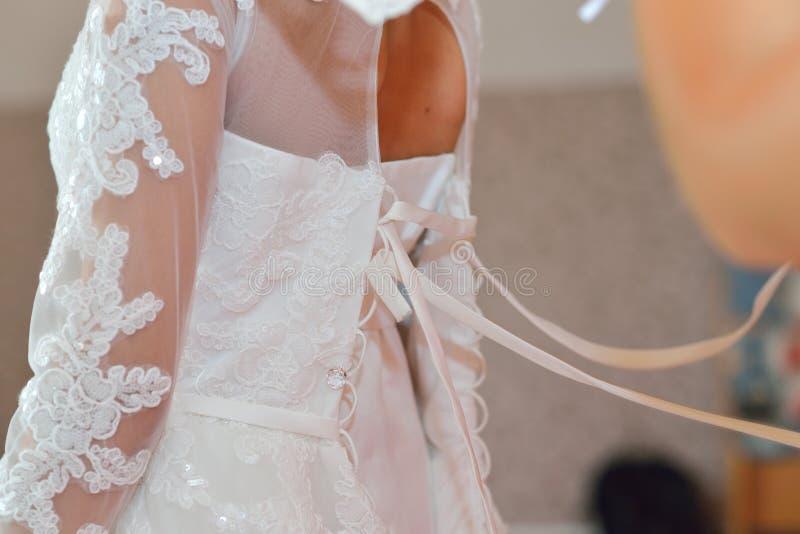 La demoiselle d'honneur aide la jeune mariée à la robe de mariage de port, vue arrière de plan rapproché photos libres de droits