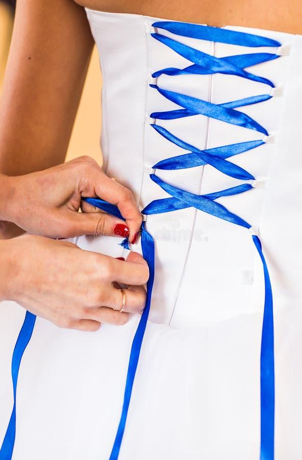 La demoiselle d'honneur aide la jeune mariée à s'habiller photos stock