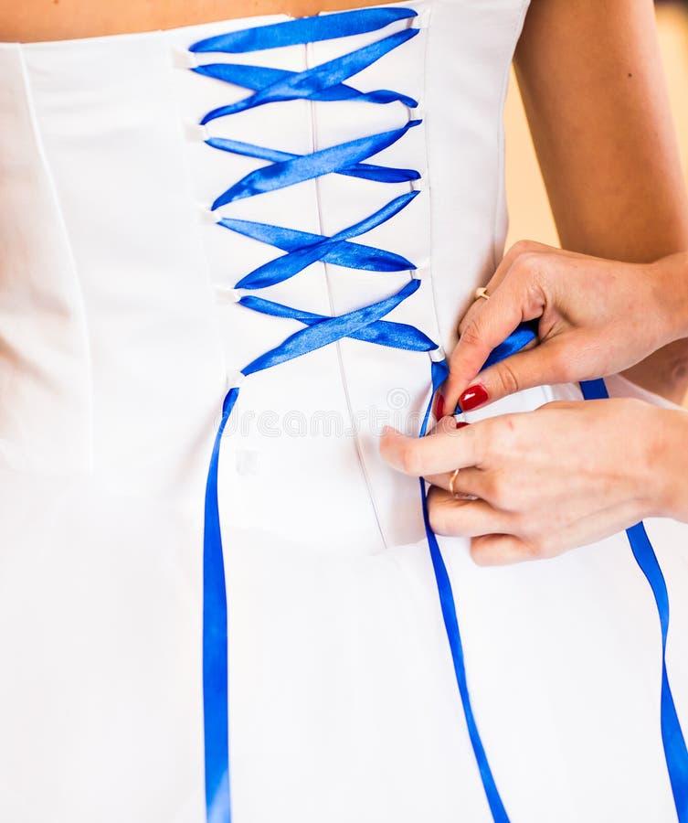 La demoiselle d'honneur aide la jeune mariée à s'habiller photographie stock