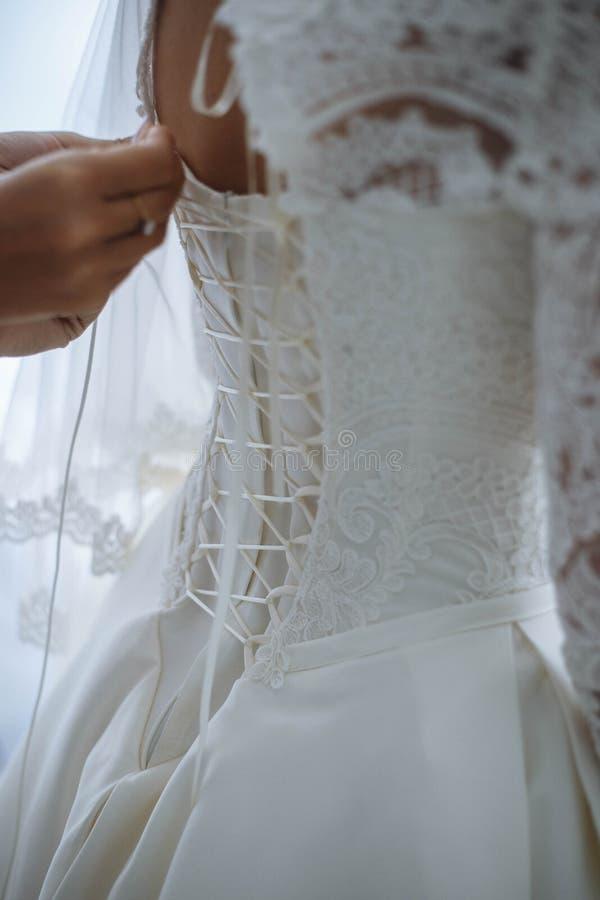 La demoiselle d'honneur habille un arc sur la robe d'une jeune mariée photographie stock