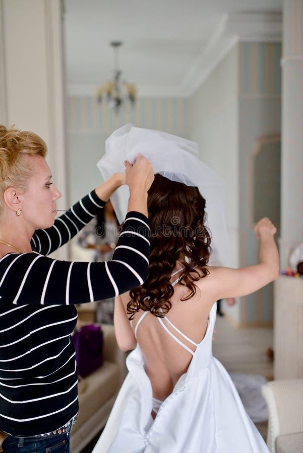La demoiselle d'honneur lace la robe de mariage blanche pour la belle jeune mariée photo stock