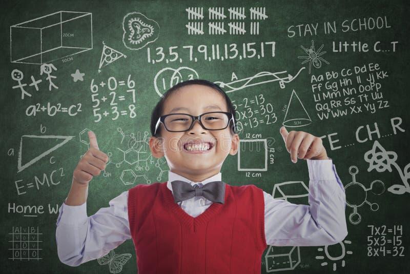 La demostración asiática del muchacho del estudiante manosea con los dedos para arriba en clase fotos de archivo