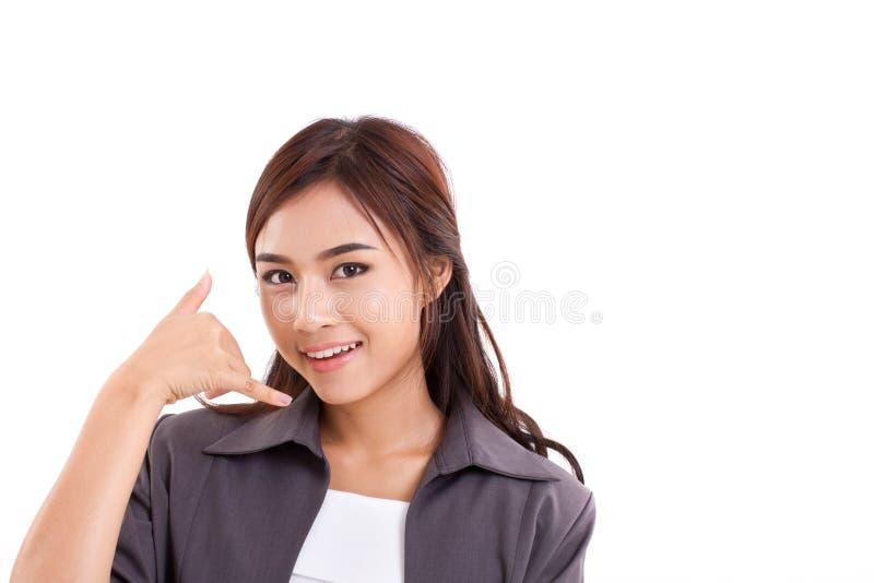 La demostración de la mujer de negocios nos llama, nos entra en contacto con gesto de mano imagen de archivo libre de regalías