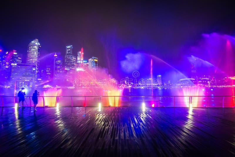La demostración del laser en las arenas de la bahía del puerto deportivo en la noche en Singapur foto de archivo