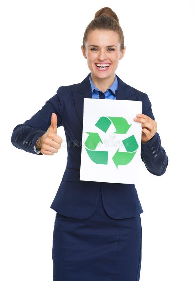 La demostración feliz de la mujer de negocios recicla la muestra y los pulgares para arriba foto de archivo libre de regalías