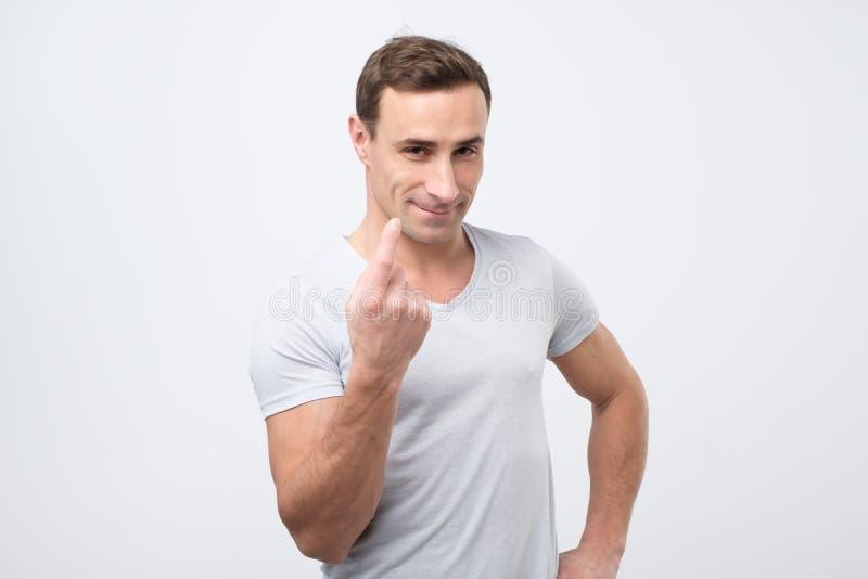 La demostración hermosa del hombre joven viene aquí gesto con el dedo índice y sonrisa sobre fondo gris imagen de archivo