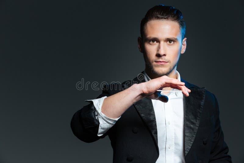 La demostración hermosa del mago del hombre joven engaña con los naipes foto de archivo libre de regalías