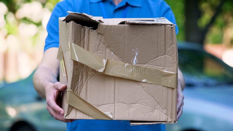 La demostración masculina del mensajero dañó la caja, entrega barata del paquete, calidad pobre del envío foto de archivo